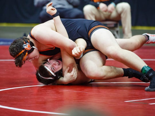 Tyler Linderbaum of Solon, top pins West Delaware, Manchester's Carson Petlon during their first round 2A 285lb match on Thursday, Feb. 15, 2018, in Des Moines.