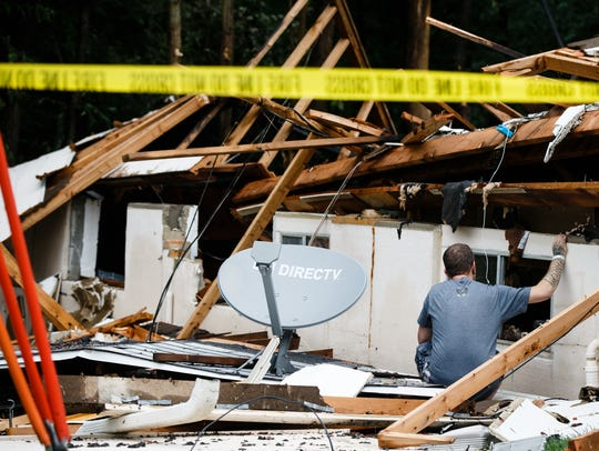 Shane Rhoades on Sunday returns to his home that exploded during a flash flood the night before the survey the damage.