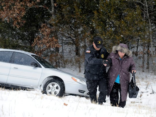 Lt. Rick Lucy, of the Baxter County Sheriff's Office, helps Donna Mullaney, of Gepp, after she lost control of her vehicle Feb. 4 on an icy stretch of the U.S. Highway 62 bypass. The Twin Lakes Area saw quite a bit of winter weather this past year.
