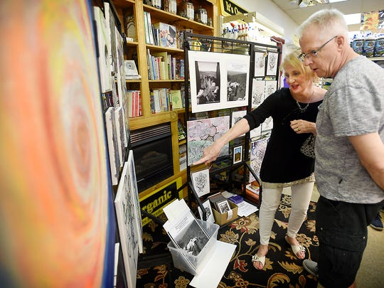 Fred and Cindy Hummel, of Lebanon, look at the artwork of Katie Trainer on display at Queen's Natural Market, 742 Cumberland St., Lebanon. The First Friday Art Walk was held Friday, July 1. Visitors could peruse art  in Lebanon at the Lebanon Valley Council on the Arts, Re:Create, Lebanon Picture Frame & Fine Art Gallery, as well as other exhibits at the Lebanon County Historical Society, Trinity United Methodist Church, and in the Mt. Gretna area at The Timbers and Gallery at La Cigale.