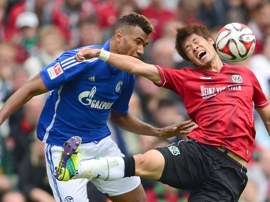 Hannover's Hiroki Sakai, right, challenges for the ball with Schalke's Eric Maxim Choupo-Moting, during the German Bundesliga soccer match between Hannover 96 and Schalke 04, in Hannover, northern Germany, Saturday Aug. 23, 2014.   (AP Photo/dpa,Peter Steffen)