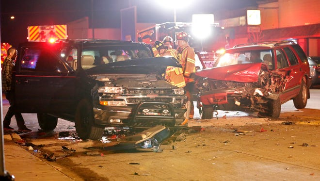 Darryn S. Shipton, far left, and members of the Fond du Lac Fire Department examine the wreckage of the two SUV's last Saturday night. The driver of the red Chevy Blazer has been arrested by Fond du Lac Police.