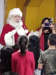 "Santa Claus singing and handing out books at ""Keep One, Share One"" event."