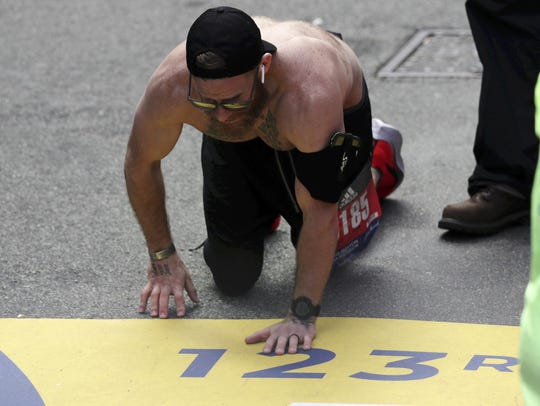 Micah Herndon, of Tallmadge, Ohio, crawls to the finish