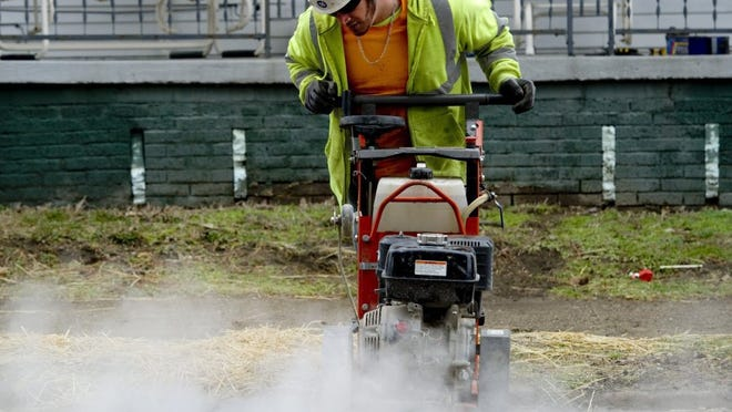 Photos by DENNY SIMMONS / COURIER & PRESS Chris Steinhauer, an employee with David Enterprises Asphalt and Paving, cuts through the asphalt along a North Third Avenue curb just north of Missouri Street Wednesday morning. Vectren is replacing gas pipelines in the area.