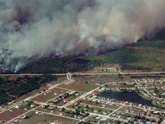 Wildfires burn out of control July 2, 1998, in Brevard and Volusia counties. Smoke from a fire drifted over a subdivision near State Road 520 in central Brevard County. Gov. Lawton Chiles said the wildfires as of July 2, 1998, had damaged or destroyed at least 86 homes in the state of Florida.