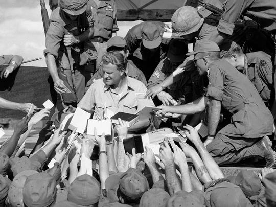 Scores of American GIs reach up to shake the hand and get his autograph after evangelist Billy Graham spoke to some 5,000 combat soldiers at the long Binh headquarters of field force II north of Saigon in South Vietnam, Dec. 22, 1966.