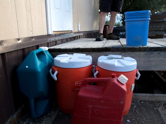 Dusty March displays some of the containers he uses to haul water from McGee Park's water station to his home in the Harvest Gold subdivision on Thursday.