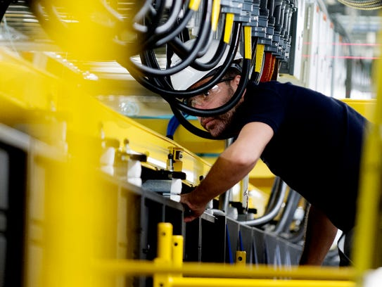 A worker looks along the rows of cabinets during the