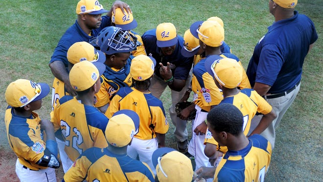 Great Lakes Region coach Jerry Houston (back center) talks to the team in the sixth inning against the Asia-Pacific Region at Howard J. Lamade Stadium.