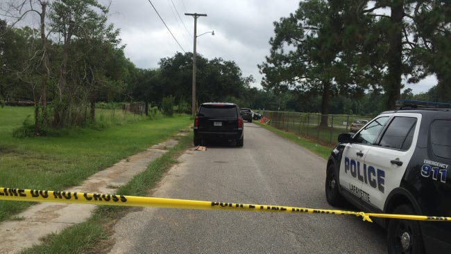 Police officers investigate the body of a discovery found along Gauthier Road in Lafayette on the morning of Aug. 3.