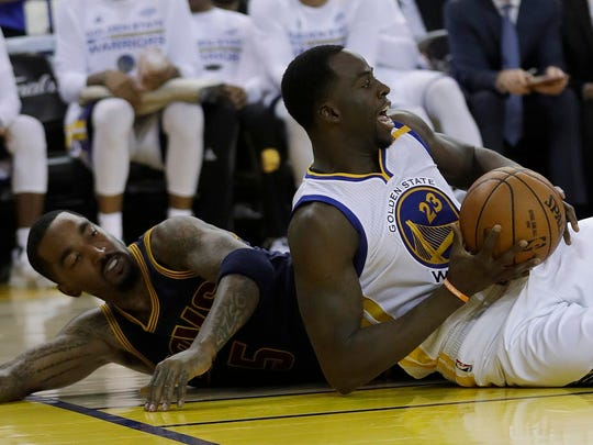 Warriors forward Draymond Green, right, controls the ball in front of Cavaliers guard J.R. Smith, left, during the second half of Game 1 of the NBA Finals in Oakland.