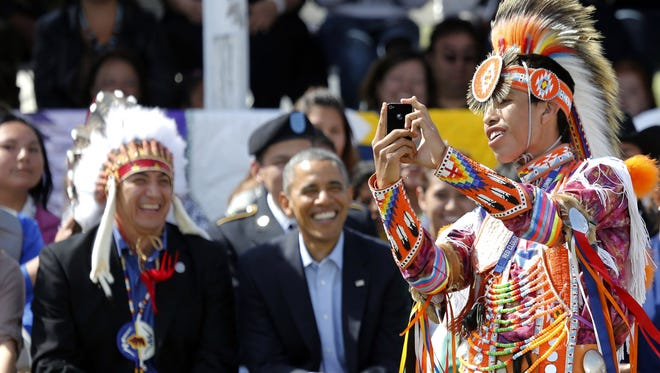 A Native American dancer creates a selfie with President Barack Obama and Chairman if the Standing Rock Sioux Tribe David Archambault, left, on the Standing Rock Indian Reservation Friday, June 13, 2014, photo in Cannon Ball, N.D. President Obama is making his first presidential visit to Indian Country for a look at two sides of Native American life, a celebration of colorful cultural traditions on the powwow grounds and a view of the often bleak modern-day conditions on tribal lands.
