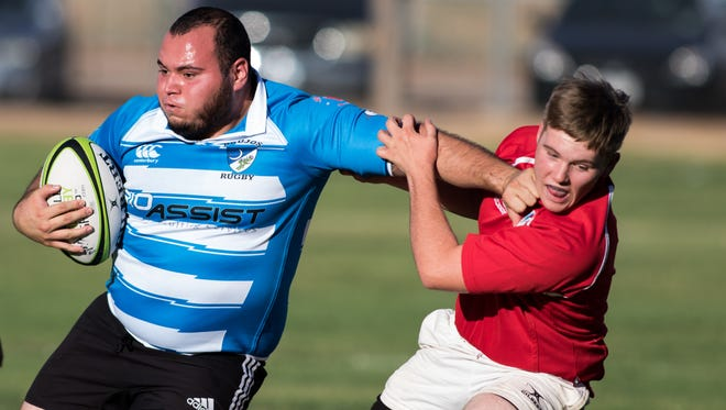 Milagro Padilla of the Albuquerque Brujos evades a tackle by Las Cruces Bulldawg Everett Salopek at the Rugby Tournament held at Burn Lake Soccer fields on August 6, 2016.