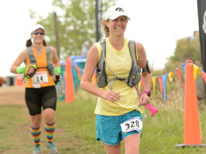 Melissa Hoskins lets out a smile as she crosses the finish line and concludes her 25-mile run during the Quad Rock Trail Race.