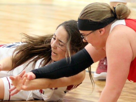 Cobre High players came away with the majority of loose balls on Saturday on their way to a 13-point victory at Deming High. Lady Cat Valarie Lopez, left, scrambles for a loose ball with Cobre's Tori Zuniga.