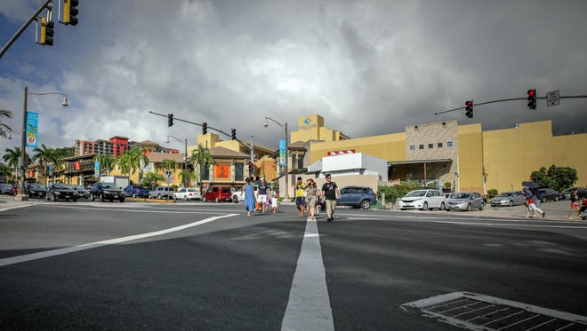 People walk across an intersection in the city of Tamuning on the island of Guam on Aug. 10, 2017.
