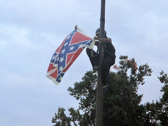 Bree Newsome of Charlotte, N.C., removes the Confederate battle flag outside the Statehouse in Columbia, S.C., on June 27, 2015. She was taken into custody when she came down.
