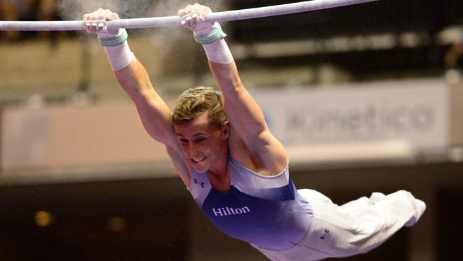 Eddie Penev competes on the  high bar during the P&G gymnastics championships at Bankers Life Fieldhouse in Indianapolis.