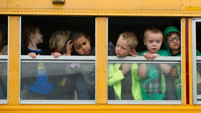 South Heights Elementary School students watch from a  school bus windows as rain falls during the dedication ceremony for East End Park on Letcher St. in Henderson, Wednesday, Sept. 28, 2016.