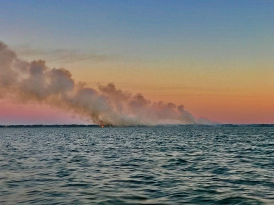 This photo was taken at sunset by St George Island Fishing Guide, Captain Krista Miller of Island Charters. It shows how far the fire stretched and you can see the flames on the right side of the smoke.