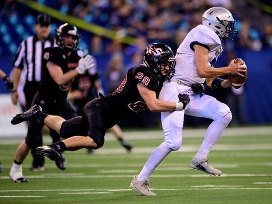 Southridge's Cole Calvert (28) prevents Woodlan's Justin Durkes (7) from making a pass during the first quarter of the IHSAA Class 2A State Championship at Lucas Oil Stadium in Indianapolis, Ind., Saturday, Nov. 25, 2017.