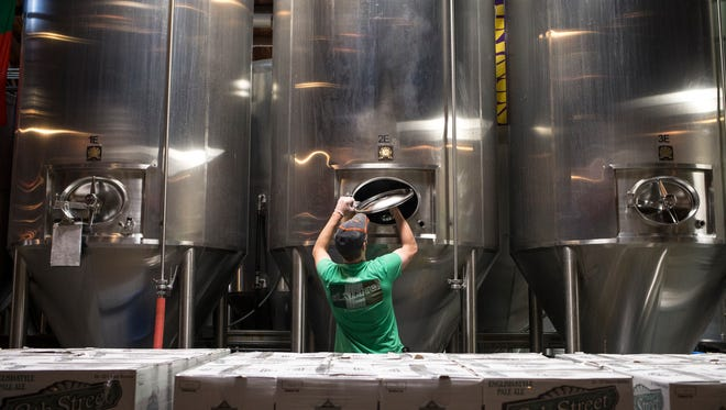Brewer Bob Grayson cleans a fermentation vessel in the brewery on Jan. 26, 2015, at Four Peaks Brewing Company in Tempe.