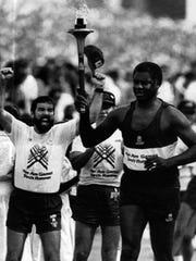 AUGUST 8, 1987: Oscar Robertson carries the torch into the Indianapolis Motor Speedway Saturday during opening ceremonies for the Pan American Games. Robertson was a member of the gold-medal winning U.S. basketball team at the 1959 Pan Am Games.
