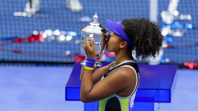 Naomi Osaka, of Japan, holds up the championship trophy after defeating Victoria Azarenka, of Belarus, in the women's singles final of the US Open tennis championships, Saturday, Sept. 12, 2020, in New York.