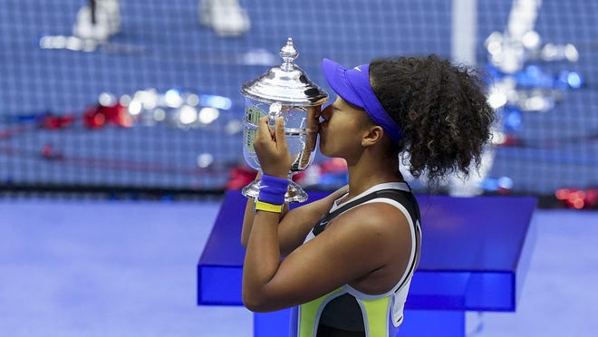 Naomi Osaka of Japan holds up the championship trophy Saturday after defeating Victoria Azarenka of Belarus in the women's singles final of the U.S. Open in New York.