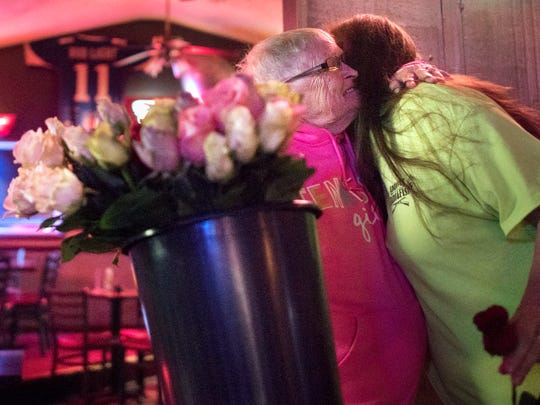 "Known as ""the rose lady"" around the Jackson nightlife scene, Brenda Scott, of Lexington, embraces her friend, Leigh Anne Gillespie, after handing her a red rose Friday, Jan. 26, 2018, at The Office Lounge in Jackson. Gillespie's late husband, Jerry ""Lil G"" Gillespie, was a regular customer of Scott's and would buy roses from her every Friday to give to his wife. In the weeks since Jerry's fatal heart attack on Sept. 19, 2017, Scott has made a point of giving Leigh Anne a rose every Friday at The Office Lounge, continuing her husband's tradition. ""She always tells me 'this is from G,'"" Leigh Anne said."