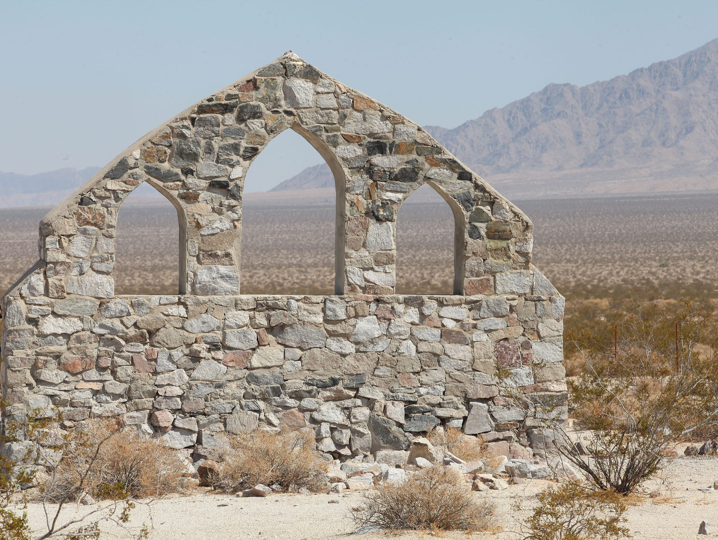 The stone wall of a chapel stands among the remnants