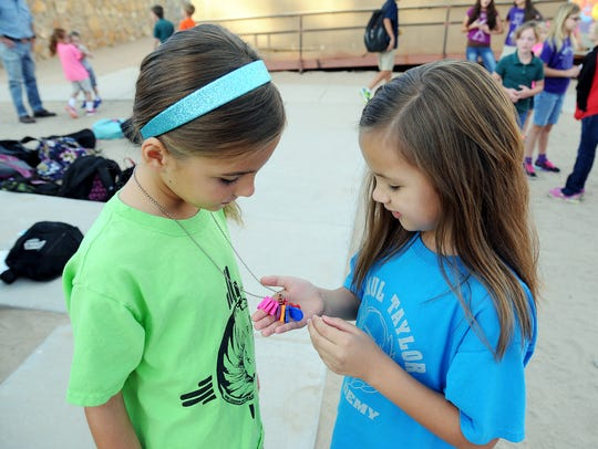 Sofia Amato, 7, left, shows her toe tokens to AJ Aizpuru,
