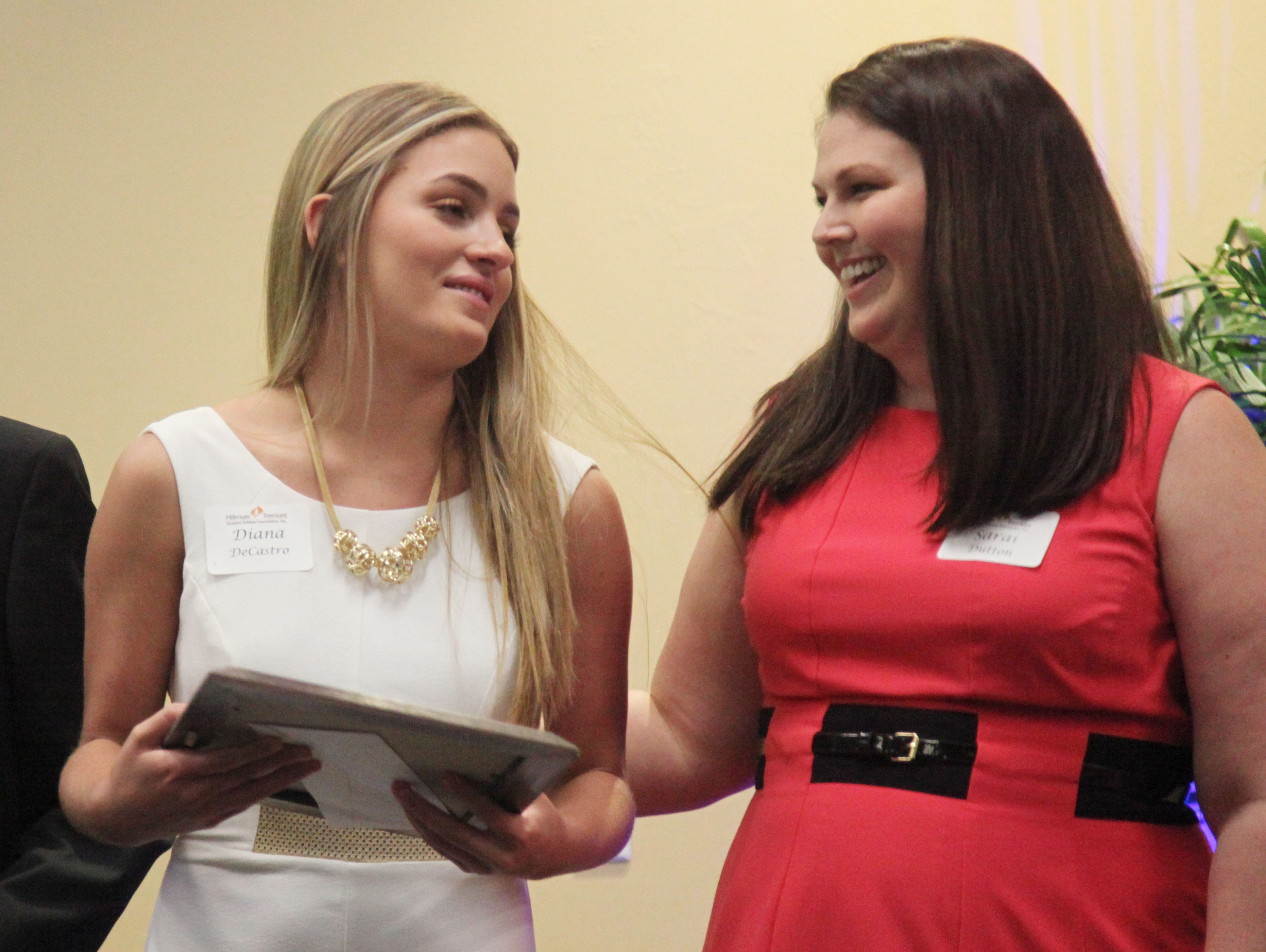 Diana DeCastro, of South Fort Myers High School is congratulated by coach Sarai Dutton during the Hillmyer-Tremont scholarship banquet at FGCU's Cohen Center on Monday.