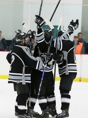 Plymouth players triumphantly raise their sticks after