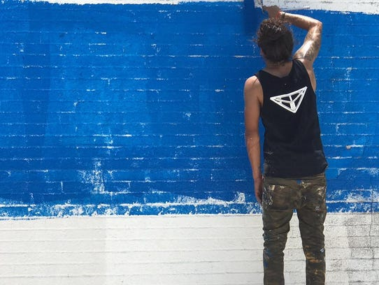 Flores preps the wall for his mural on Mesquite and