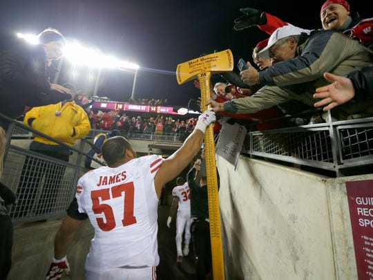 Wisconsin Badgers defensive end Alec James celebrates with the Paul Bunyan Axe.