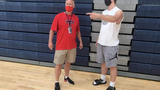 Truman High School boys basketball coach Rod Briggs, left, and senior forward Max Black get together before Wednesday morning's practice in the high school gymnasium. Briggs is turning the session over to Black who will lead his teammates through practice.