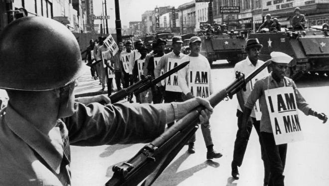 National Guard bayonets block Memphis' famed Beale Street on March 29, 1968, as marchers supporting striking sanitation workers pass through downtown. A march led by Dr. Martin Luther King Jr. the day before erupted in violence.