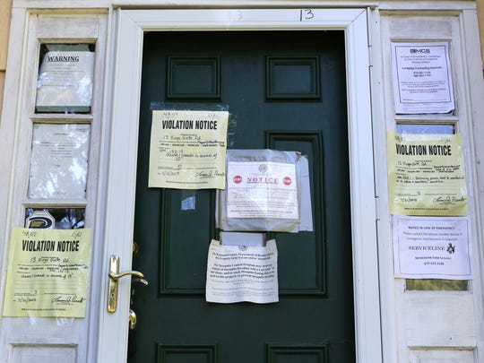 Jerry Waxenberg of Montebello says the house next door was abandoned after Hurricane Irene in 2011 and is creating all kinds of problems, which are being ignored by the bank holding the mortgage and local officials. Violation notices on the abandoned house, September 15, 2015.