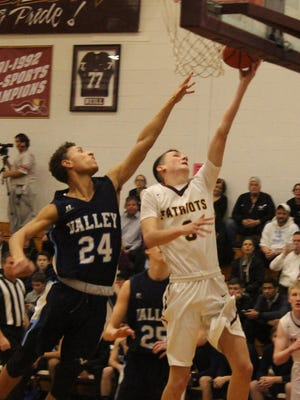Justin Wills of Wayne Hills going for a layup as Wayne Valley's Mark Howell defends.