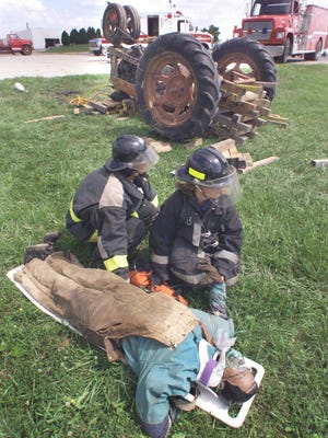 Volunteer firefighters pause after extracting a mannequin from beneath an overturned tractor during a demonstration at the National Education Center for Agricultural Safety.