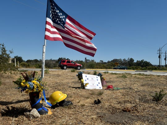 STAR FILE PHOTO A U.S. flag waves over a makeshift memorial in September 2016 at a roundabout on Highway 246 east of Lompoc, where Ventura County firefighter Ryan Osler died in a crash while responding to a wildfire.