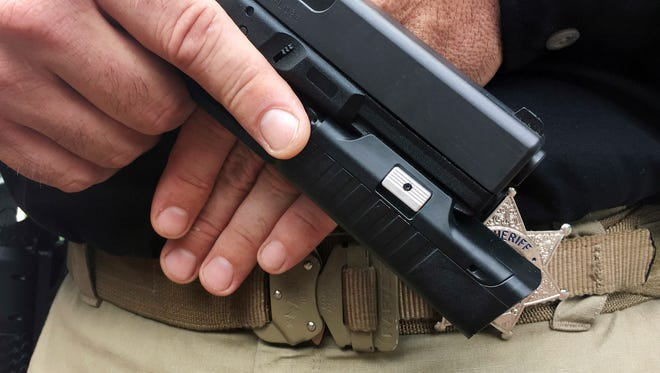 In this Sept. 23, 2017 photo provided by Centinel Solutions, a model displays a camera mounted below the barrel of a handgun in New York. Some police departments are considering putting cameras on officers' guns, saying they would give a better, unobstructed view of police-involved shootings and save money on video storage costs compared with body cameras.