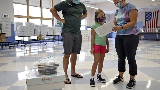 Fourth grader Rose Ritzman, 9, and her father, Kurt, look over her schedule with her homeroom teacher, Sarah Hoepf, while picking up supplies for the year at Edison Intermediate & Larson Middle School in Grandview Heights on August 11, 2020. Rose and her dad were also picking up supplies for her sister, Charlotte, who is in the sixth grade, and brother, Ben, who is in the eighth grade.