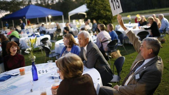 In 2019, people gathered on the lawn at the Oconee campus of UNG for Oconeefest in this scene showing a man making a bid during the raffle. This year the festival is online.