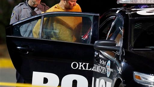 Christian Costello, son of Oklahoma Labor Commissioner Mark Costello, is placed in a police car, Sunday, Aug. 23, 2015, at the scene where Mark Costello was fatally stabbed in Oklahoma City. Christian Costello was arrested on a first-degree murder complaint, police said.