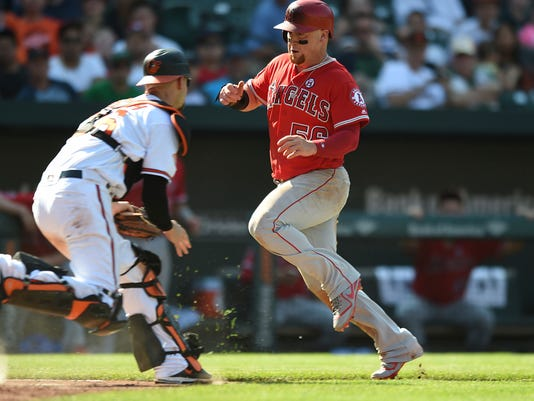 Los Angeles Angels' Kole Calhoun, right, eludes the tag of Baltimore Orioles' Caleb Joseph to score the go ahead run in the eighth inning of a baseball game, Sunday, Aug. 20, 2017, in Baltimore. The Angels won 5-4. (AP Photo/Gail Burton)