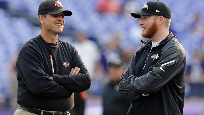 San Francisco 49ers head coach Jim Harbaugh, left, chats with his son Jay, a Baltimore Ravens offensive assistant, before an NFL preseason football game, Thursday, Aug. 7, 2014, in Baltimore.