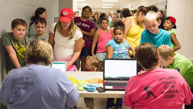 United Way representatives help students and parents register for backpacks and school supplies at the Back-to School Bash in Fairview August 5, 2017.